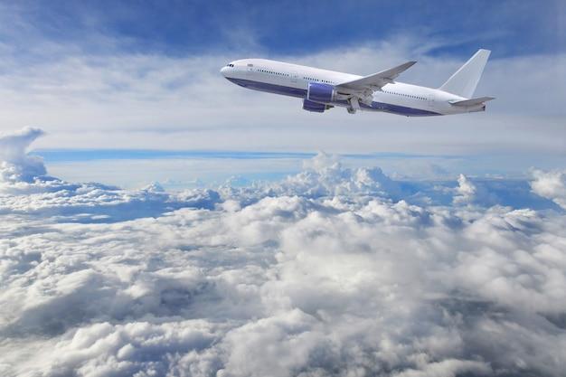 L'aeroplano decolla sui precedenti delle nuvole e del cielo blu Foto Premium