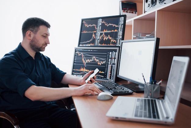 L'agente di cambio in camicia lavora in una sala di monitoraggio con schermi di visualizzazione. grafico di borsa forex trading finanza. uomini d'affari che scambiano titoli online Foto Premium