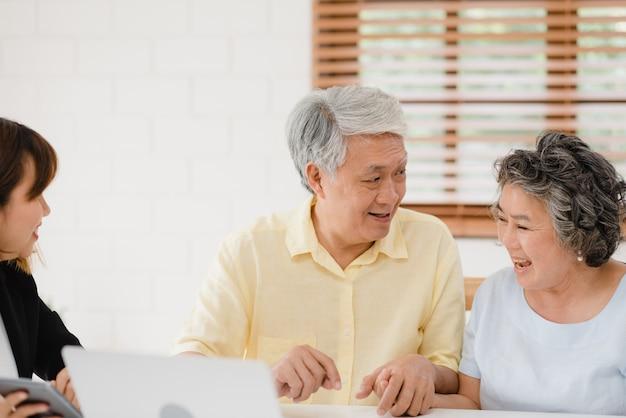 L'agente femminile intelligente asia offre assicurazioni sanitarie per coppie anziane tramite documenti, tablet e laptop. Foto Gratuite
