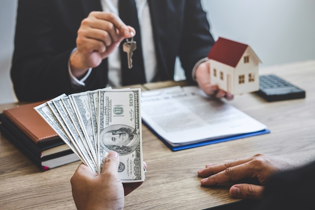 L'agente immobiliare riceve denaro dal cliente dopo aver firmato un contratto con proprietà approvate Foto Premium