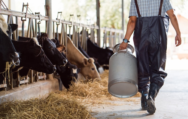 L'agricoltore asiatico sta tenendo un contenitore di latte sulla sua azienda agricola che cammina fuori dalla fattoria Foto Premium