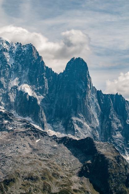 L'aiguilles des drus accanto all'aiguille verte sopra la valle di chamonix con nuvole e cielo blu Foto Gratuite