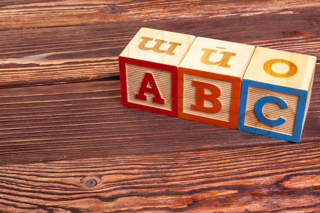 L'alfabeto in legno del blocco pone sul pavimento di legno Foto Premium