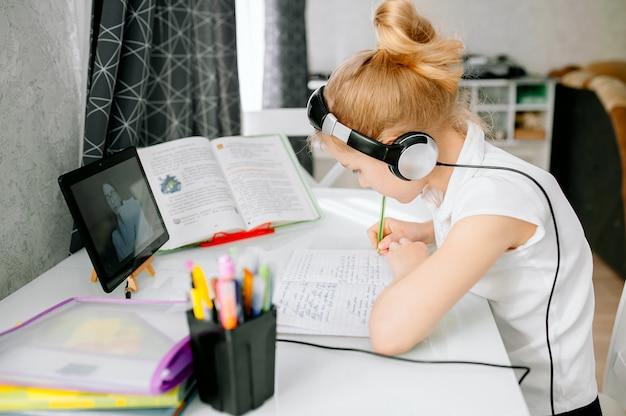 L'allievo scolastico teenager della ragazza indossa la teleconferenza delle cuffie che studia online con l'insegnante a distanza da casa. studente adolescente che utilizza computer portatile che parla nella video chat della webcam che impara lezione con l'insegnante a distanza. Foto Premium