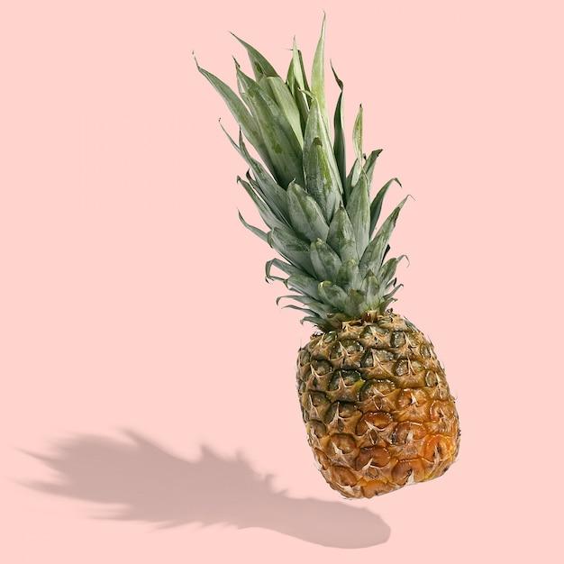 L'ananas vola nell'aria sul layout creativo luminoso, copia spazio Foto Premium