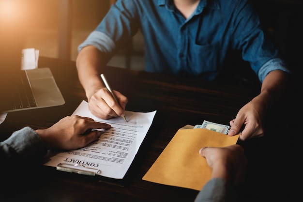 L'appaltatore consegna denaro in una busta ad un altro uomo d'affari e indica il contratto di autorizzazione del segno. Foto Premium