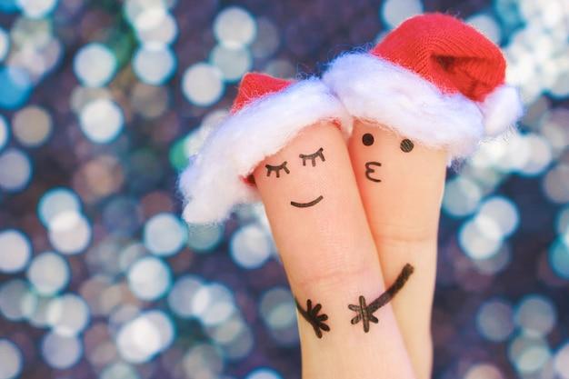 L'arte delle dita delle coppie celebra il natale. concetto di uomo e donna abbraccio in cappelli di capodanno. Foto Premium