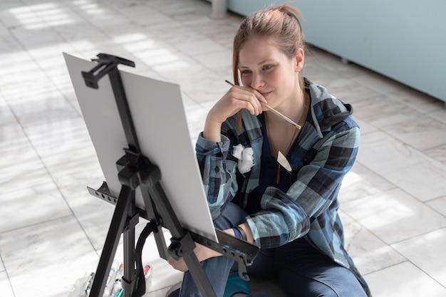 L'artista della giovane donna dell'adolescente dipinge con le pitture ad olio che si siedono sul pavimento di marmo. tela bianca e cavalletto si trovano sul pavimento di piastrelle di marmo nella stanza con pareti turchesi e verde chiaro. Foto Premium
