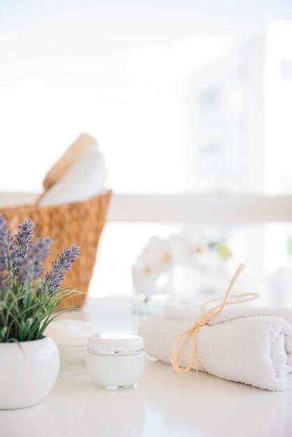 L'asciugamano e la crema vicino alla lavanda fiorisce sulla tavola bianca Foto Gratuite