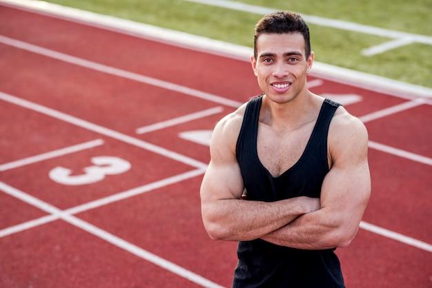 L'atleta bello sorridente in un'attrezzatura sportiva con le sue armi ha attraversato sulla pista di corsa che esamina la macchina fotografica Foto Gratuite