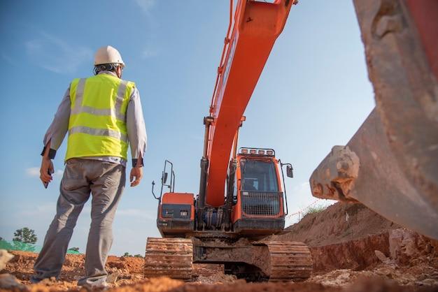 L'attrezzatura di protezione personale di usura dell'ingegnere di costruzione sta al sito della costruzione della strada Foto Premium