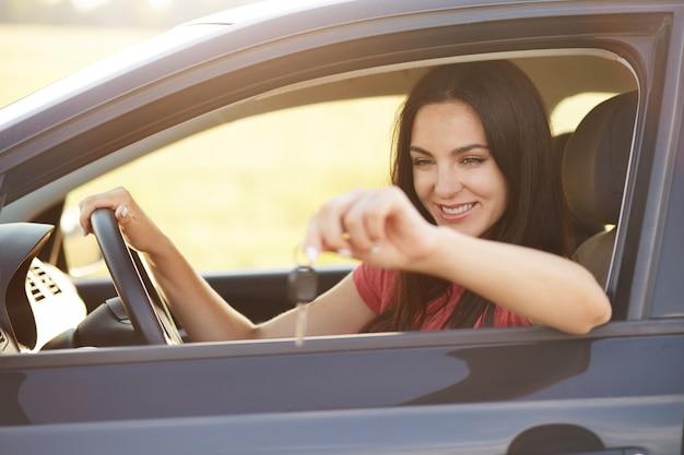 L'autista femminile felice tiene le chiavi dall'automobile Foto Gratuite