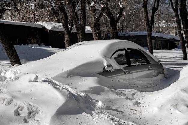 L'auto d'argento è nel parcheggio in un grande banco di neve. problemi meteorologici Foto Premium