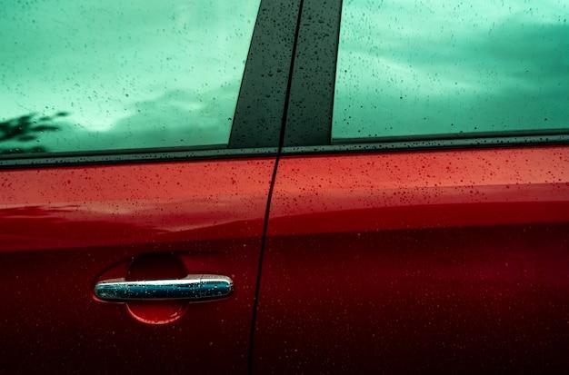 L'auto rossa sta lavando con acqua. attività nel settore automobilistico. auto con gocce d'acqua dopo la pulizia con acqua. pulizia dell'automobile prima del servizio di sciolinatura. servizio di pulizia del veicolo. Foto Premium