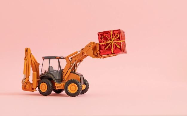 L'escavatore giocattolo trasporta un contenitore di regalo legato con un arco. sfondo rosa. copia spazio, Foto Premium