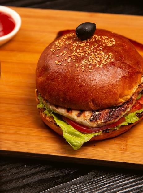 L'hamburger di carne di pollo con pomodoro e lattuga all'interno è servito con olive nere e ketchup su un vassoio di legno. Foto Gratuite