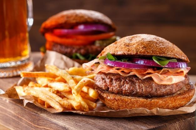 L'hamburger e le patate fritte si chiudono su su fondo di legno. Foto Premium