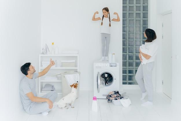 L'immagine del piccolo bambino felice alza le braccia, mostra bicipiti e forza, il padre mostra come segno con il pollice in su, sta nella stanza di lavaggio con un mucchio di vestiti nel bacino vicino alla lavatrice, detersivo. lavoro ben fatto Foto Premium