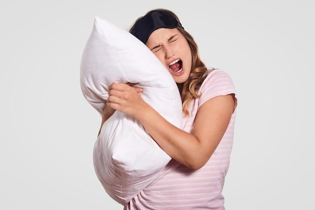 L'immagine della donna sbadiglia come ha l'espressione assonnata, indossa abiti domestici, porta morbido cuscino bianco, pone su bianco. persone, riposo, comfort, stanchezza, concetto di sonno Foto Gratuite