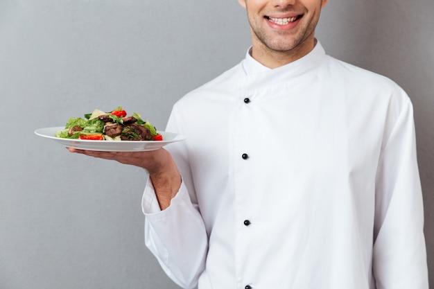 L'immagine potata di un cuoco unico maschio sorridente si è vestita in uniforme Foto Gratuite
