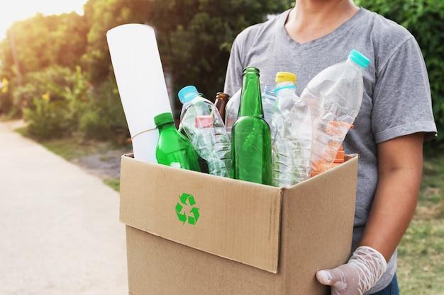 L'immondizia della scatola della tenuta della mano della donna per ricicla Foto Premium