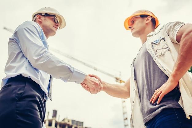L'ingegnere dell'architetto che stringe la mano passa l'altra mano al cantiere. lavoro di squadra di affari, cooperazione, concetto di collaborazione di successo Foto Premium