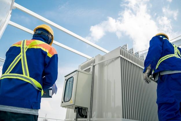 L'ingegnere di potere elettrico controlla il trasformatore elettrico nel cantiere Foto Premium