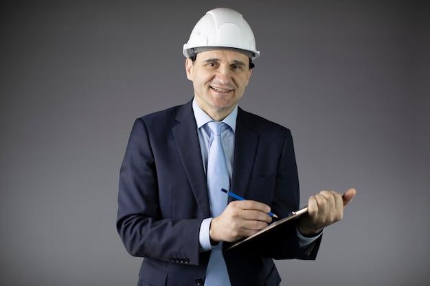 L'ingegnere petrolifero in elmetto prende appunti e guarda la telecamera con un sorriso Foto Premium