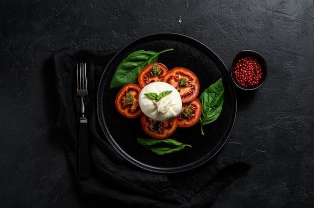 L'insalata dei pomodori e del burrata è servito sulla banda nera. sfondo scuro vista dall'alto. spazio per il testo Foto Premium