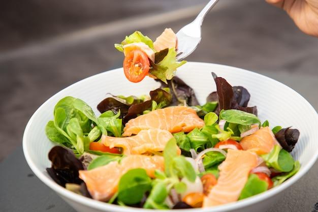 L'insalata di salmone fresca con pomodori dolci, aglio sottaceto, cipolle e spinaci è una dieta sana per ogni pasto. Foto Premium