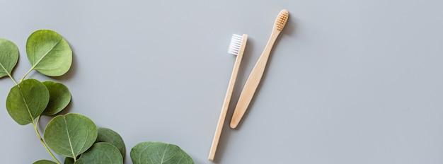 L'insegna di web con il piano di bambù naturale degli spazzolini da denti di eco mette su fondo grigio Foto Premium
