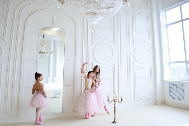 L'insegnante allena il balletto con le bambine in abiti rosa nella stanza Foto Gratuite
