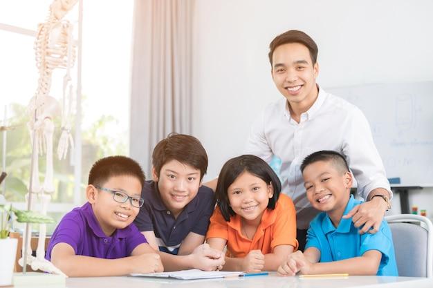 L'insegnante asiatica spiega una struttura del corpo umano a un piccolo allievo Foto Premium