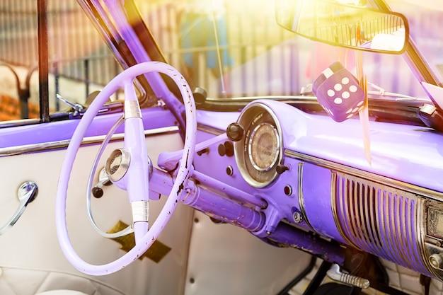 L'interno classico d'annata porpora dell'automobile americana ha parcheggiato sulla via di vecchia avana Foto Premium