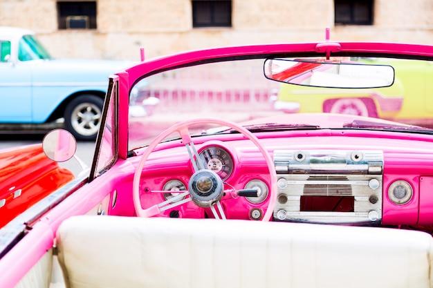 L'interno classico d'annata rosa dell'automobile americana ha parcheggiato sulla via di vecchia avana Foto Premium