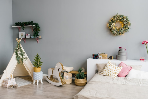 L'interno della camera da letto o della stanza dei bambini decorato per natale o capodanno: letto, wigwam, cavallo a dondolo per bambini, ghirlanda di natale sul muro Foto Premium