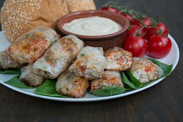 L'involtino primavera con carne e verdure è servito su un piatto bianco con salsa. Foto Premium
