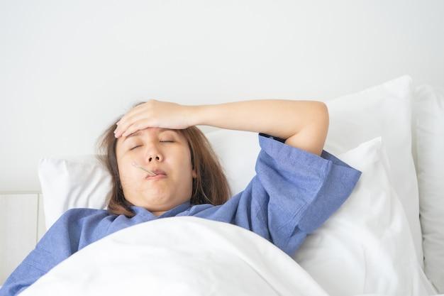 L'ipotermia asiatica bella donna è stata misurata dalla febbre. sdraiarsi sul letto Foto Premium