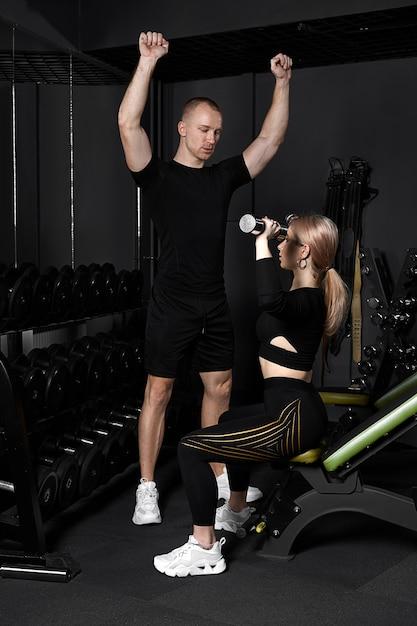 L'istruttore di fitness conduce un allenamento personale per una ragazza con manubri davanti allo specchio Foto Premium