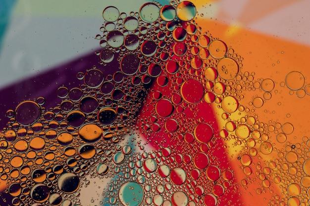 L'olio cade in acqua su uno sfondo colorato Foto Gratuite