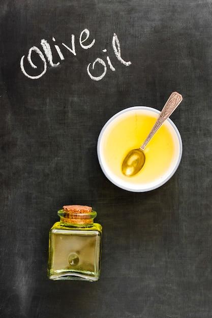 L'olio d'oliva in ciotola e bottiglia chiuse con sughero sulla lavagna Foto Gratuite