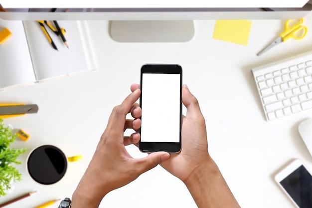 L'oman passa lo smart phone della tenuta con lo schermo in bianco dello spazio della copia sulla scrivania. Foto Premium