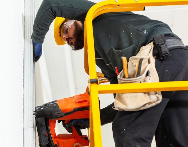 L'operaio costruisce un muro di cartongesso Foto Premium