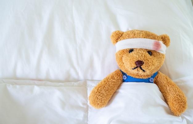 L'orsacchiotto era malato a letto dopo essere rimasto ferito in un incidente. ottenere l'assicurazione sulla vita e il concetto di assicurazione contro gli infortuni Foto Premium
