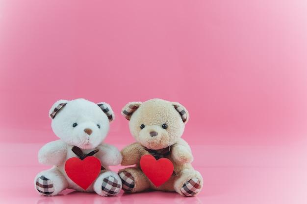 L'orso adorabile delle coppie tiene il cuore con fondo rosa Foto Premium
