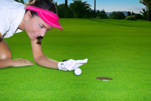 L'umore della donna del foro verde di golf che passa rapidamente passa una palla Foto Premium