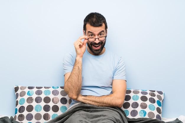 L'uomo a letto con gli occhiali e sorpreso Foto Premium