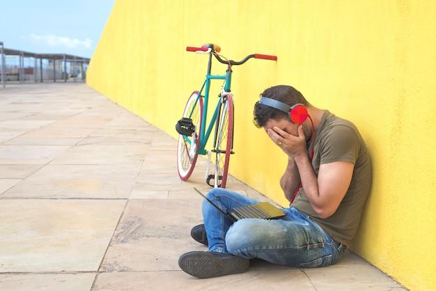 L'uomo abbandonato ha perso nella depressione seduto su una strada di terra che soffriva di dolore emotivo, tristezza e sembrava distrutto e disperato appoggiandosi al muro da solo Foto Premium