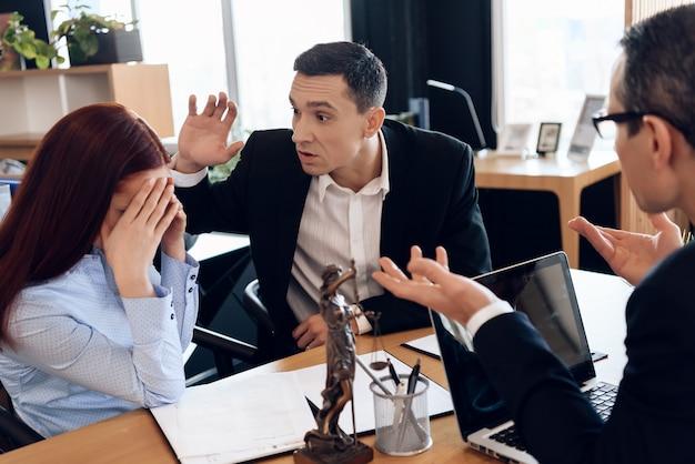 L'uomo adulto ha alzato la mano sulla donna che si siede all'ufficio degli avvocati Foto Premium