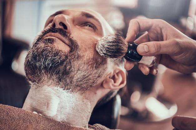 L'uomo adulto si rade in un elegante barbiere Foto Premium